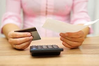 woman is holding bill and credit card in hands