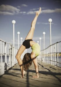 Young girl doing gymnastic exercises on the pier (ancient version)