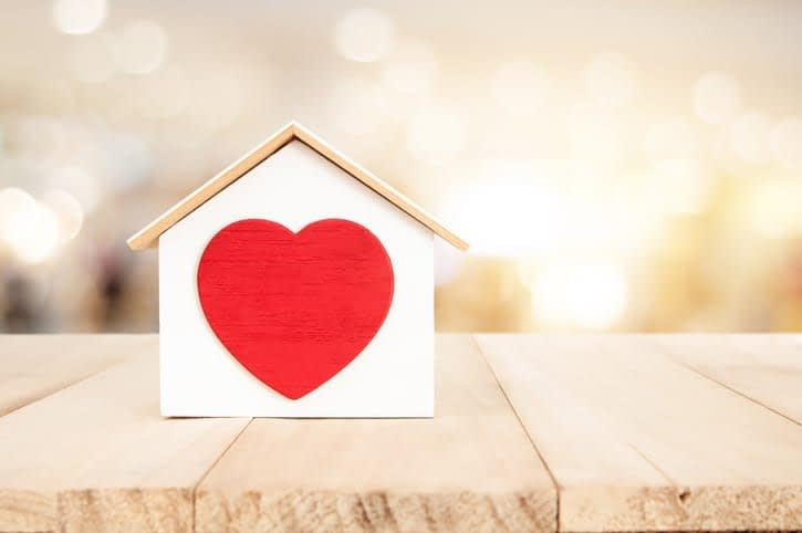 Small house on a wooden floor with a big red heart in the center.
