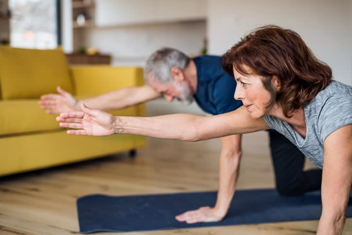 senior couple exercising in their home