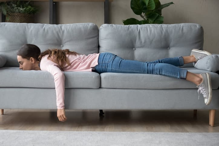girl stretched out on a couch feeling overwhelmed