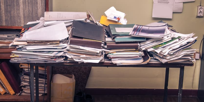 Piles of paper on top of a desk