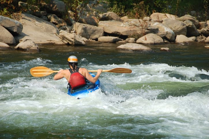 kayaker navigating change in the rapids
